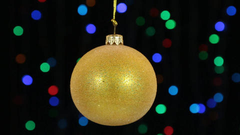 Close-up, the rotation of a yellow Christmas ball hanged on a golden rope Footage