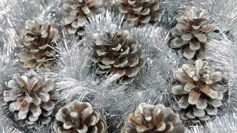 Close-up of the rotation of silver tinsel and silver pine cones. Christmas Footage