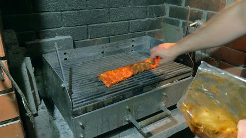 male hand laying seasoned marinated juicy pork spare ribs slowly on hot grill Live Action