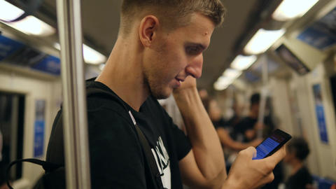 Young Adult Caucasian Man Riding a Metro Subway Train and Texting on His Mobile Footage