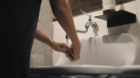 Woman Washing Her Hands in Sink in Loft Style Bathroom with Brick Walls. 4K Footage