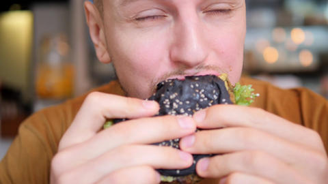 Young Hipster Man Enjoys Eating And Tasting Delicious Vegetarian Burger 4K Close Live Action
