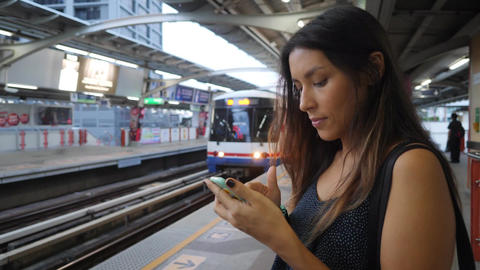 Attractive Young Mixed Race Girl Texting on Mobile Phone while Waiting for BTS Footage