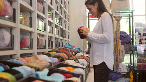 Young Mixed Race Woman Choosing Yarn for Knitting in Shop for Hobby and Handmade Footage