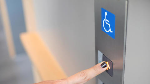 Female Finger Pressing Elevator Lift Button for the Disabled in Shopping Mall or Footage