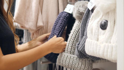 Young Mixed Race Woman Choosing Knitted Winter Hat at Clothing Store in Shopping Footage