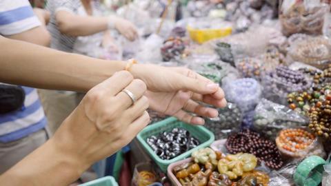 Young Woman Shopping Handmade Bracelet Jewelry at Asian Night Market. Bangkok Footage