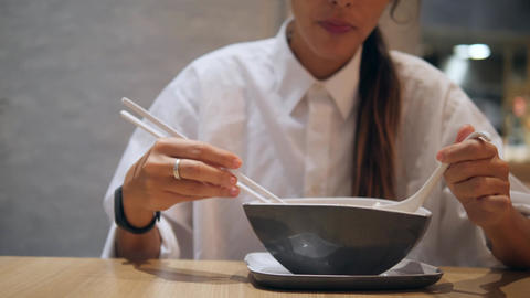 Asian Tourist Girl Eating with Chopsticks Traditional Tom Yam Noodle Soup in Footage