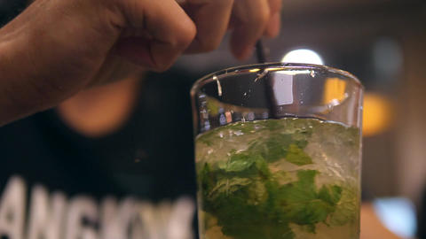 Young Man Drinking Mixing and Drinking Fresh Mint Mohito Cocktail in Bar at Footage
