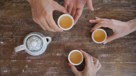 Human Hands Taking Tea Cups from Wooden Rustic Table and Drinking Traditional Footage