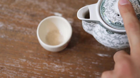 Male Hand Pouring Healthy Green Tea from Teapot in Vintage Cup on the Wooden Footage