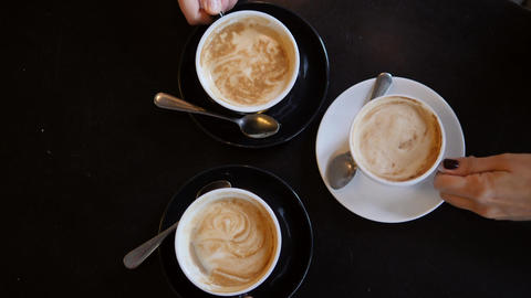 Hands Taking Cups with Cappuccino Coffee from Black Table in Cafe. View from Footage