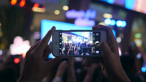 Womans Hands Holding Mobile Phone and Taking Photo of Concert Stage. Blured Blue Footage