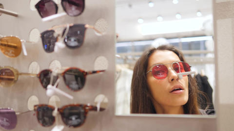 Young Attractive Mixed Race Girl Trying Sunglasses near Mirror in Shopping Mall Footage
