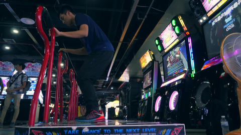 Young Asian Man Playing Dance Revolution Game and Doing Dancing Tricks on Arcade Footage