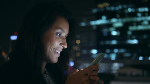 Young Smiling Woman Texting on Mobile Phone at Night in City. 4K. Attractive Footage