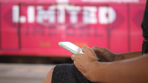 Young Woman Sitting on a Bench at Metro Subway Station and Texting on Mobile Footage