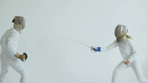 Young woman fencer having fencing training with trainer in white studio indoors Footage