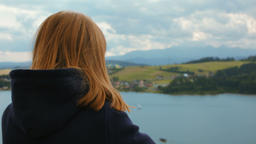 The red-haired Young Women is Watching at the Lake and the Mountain Village ビデオ