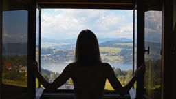 Young Lady Opens the Window and Looks at the Mountains, Lake, Village and Sky Footage