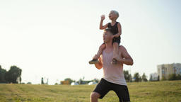 Boy is Playing Ball while Sitting on Father's Shoulders on grass during Sunset Footage