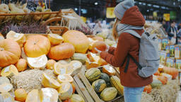Lady is Choosing Pumpkin on Stand with Vegetables for Fall Holiday Halloween Archivo