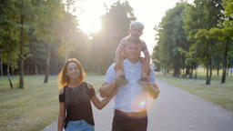 Happy Young Family is Walking in Park with the Son Sitting on Daddy's Shoulders Footage