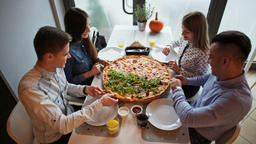 Young Friends are Eating a Huge Pizza at the Restaurant, Talking and Laughing Footage