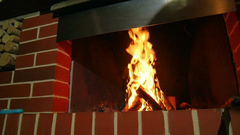 Indor open fireplace burning and heating up guests room. Logs burning in home Footage