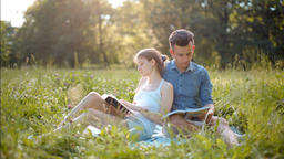 Young Beautiful Couple Reading Books Outdoors in Summer, Smiling and Kissing Footage