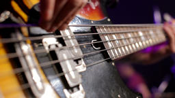CloseUp of Musician Playing the Bass Guitar at Concert in Nightclub with Light Footage