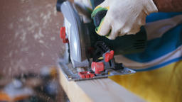 The Man is Sawing Wood Board with Electric Rotary Buzz Saw Tool in his Workshop Footage