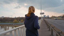 SlowMotion of Nice Young Lady in Sportswear Running on a Bridge in the City Footage