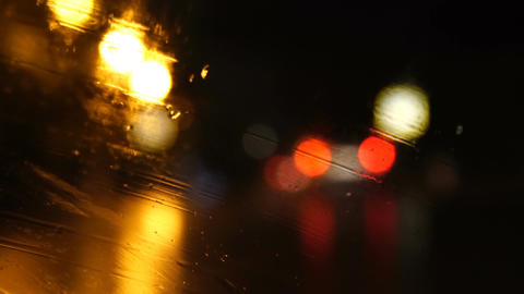 Night city in the lights of street lamps. Defocused view through a wet glass Footage