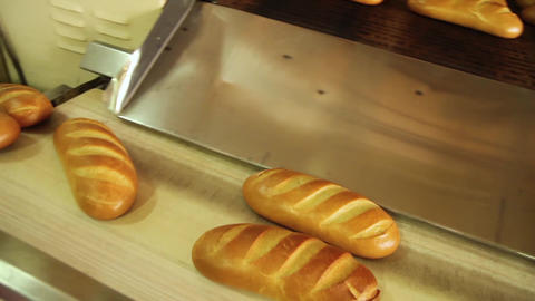 Camera follows a loaf of bread on conveyor belt Live Action