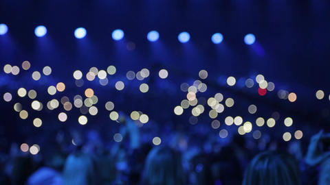 Audience is shining with flashlights of phones Footage