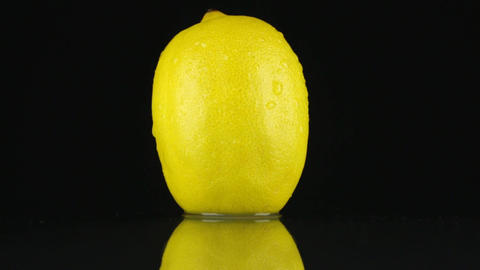 Yellow lemon in drops of dew rotates on its axis. HD Footage