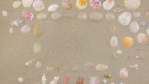 Wind blows away sand from stones and sea shells, top view Footage