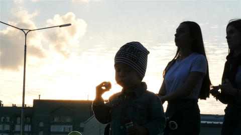 Slow Motion Little Boy Silhouette Blows Bubbles against Sunset Footage
