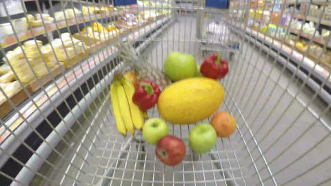 Shopping trolley with fresh vegetables and fruits moving through supermarket Footage