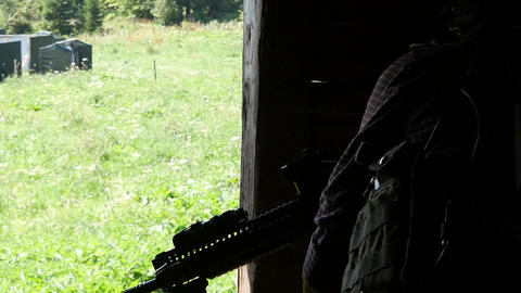 Soldier who has an assault weapon in his hand housed the wall of a house near Live Action