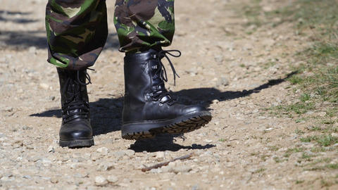 Military who is wearing black boots that rarely walk on the road in the ground Live Action