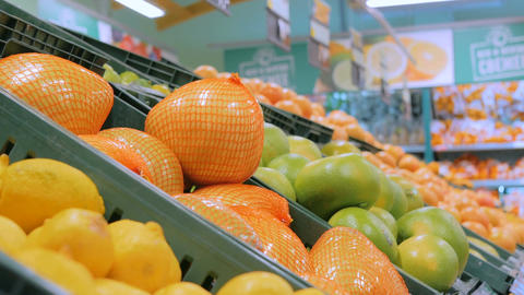 Woman buying fresh exotic citrus fruits at grocery store Footage