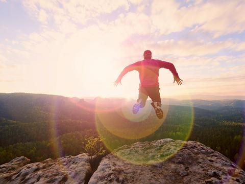 Man jumping from the mountain edge. Man jumping off a cliff without rope. Risky Photo