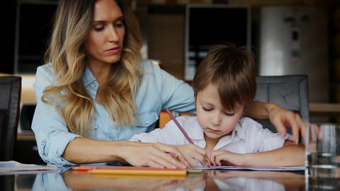 Beautiful mom helps her son to paint with colored pencils image. Helping to Live Action