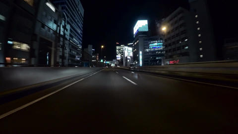 Driver view through the illuminated nightlife buildings and signs of Roppongi di Footage