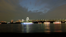Time lapse of illuminated party boats gathering off the coast of Tokyo at twilig Footage