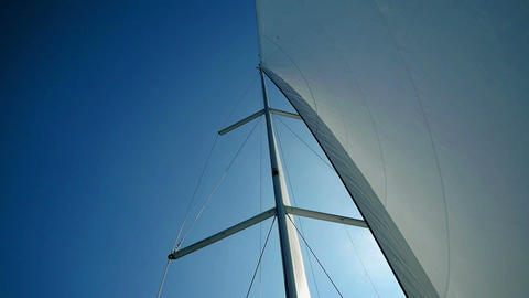Sailing boat main mast with perfectly curved main sail and blue sky behind Live Action