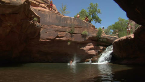 Man does flip off of red rock cliffs into water Footage