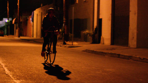 Girl rides bicycle down a dark street at night Footage